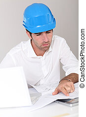 Site manager in office with security helmet