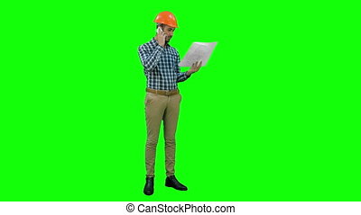 Site manager talking on mobile phone holding blueprints on a Green Screen, Chroma Key.