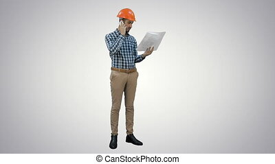 Site manager talking on mobile phone holding blueprints on white background.