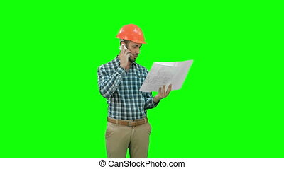 Site manager talking on the phone holding blueprints on a Green Screen, Chroma Key.