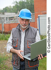 Site manager with laptop computer checking construction