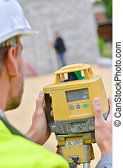 Site surveyor taking measurements
