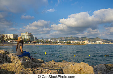 The woman on a pier looks at the city of Sitges