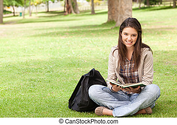 sittande, lärobok, medan, tonåring, holdingen, le