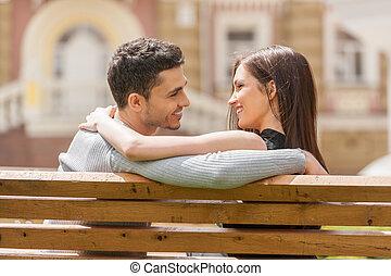 sittande, par, ung, bänk, glad, annat, bench., varje, nära, le, älskande, baksidaen beskådar
