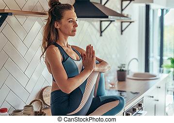 sittin, 若い, テーブル, kitchen., 女, ヨガ, 練習する