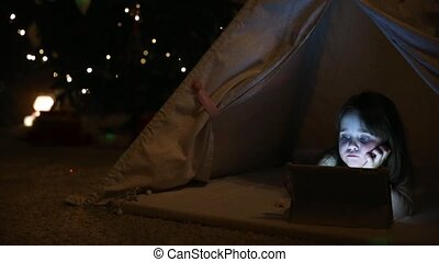 Sitting at home in a tent against the background of a Christmas tree, a little girl lying on the floor clicks on the screen of an electronic tablet.