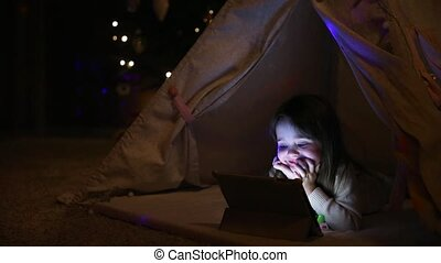 Sitting at home in a tent against the background of a Christmas tree, a little girl lying on the floor watching cartoons, smiling with teeth and laughing out loud.