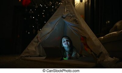 Sitting at home in a tent against the background of a Christmas tree a little girl lying on the floor examines her new gift, learns to use a tablet computer