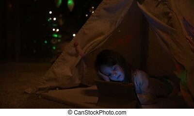 Sitting at home in a tent against the background of a Christmas tree, a little girl lying on the floor holds onto her head, and with the other hand she presses the screen of the electronic tablet.