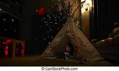Sitting at home in a tent against the background of a Christmas tree, a little girl lying on the floor talking on video communication, learns to use a tablet computer. Average plan
