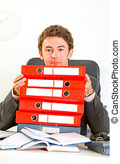 Sitting at office desk confused modern businessman looking out from pile of folders