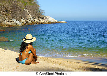 Young woman sitting at the beach looking over the ocean.