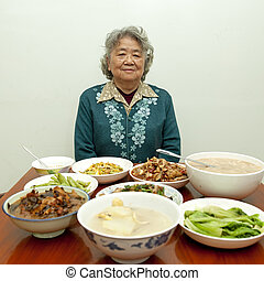 Sitting at the dinner table, happy grandmother