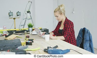 Sitting at workbench female using laptop