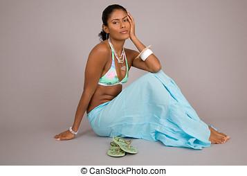 Sitting beauty - Beautiful brazilian woman sitting on grey...