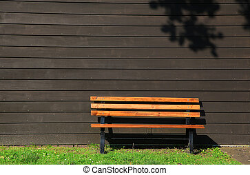 Sitting bench by brown siding wall