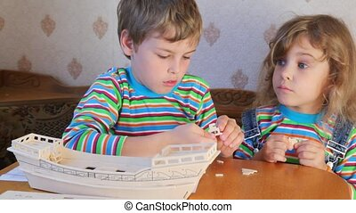 sitting boy and girl constructing toy model of ship
