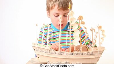 sitting boy fasten cables to toy model of ship on white...
