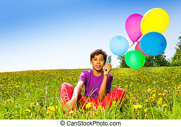 Sitting boy with flying balloons in summer
