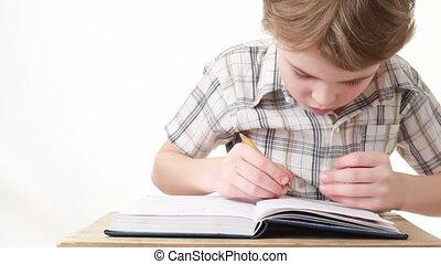 sitting boy writing on notebook on white background