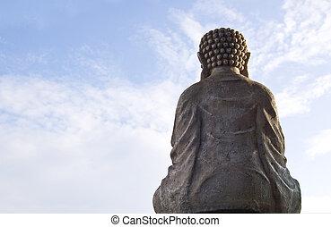 Sitting Buddha image on blue sky background.