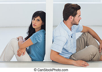 Sitting couple are separated by wall with woman looking at...