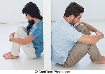 Sitting couple are separated by white wall and looking...