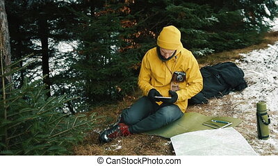 Sitting down the mountain hill next to the green trees a young man is looking for a new road. He is holding an tablet, a map, a camera and a thermos