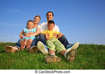 sitting family grass sky