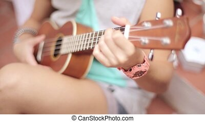 Sitting girl in shorts playing brown ukulele guitar on street. Summer sunny day. Music. Strings. Sound. Song