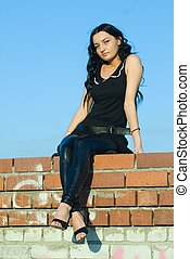 Sitting girl on roof wall
