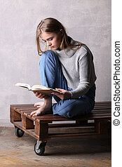 Sitting girl reading a book. Gray background