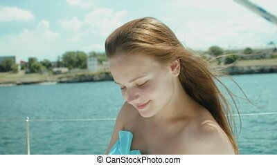 Sitting girl sunbathes on the yacht which moving in the sea