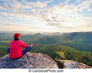 Sitting hiker on rock. Man in red black warm clothes is sitting on cliff and enjoying far view.
