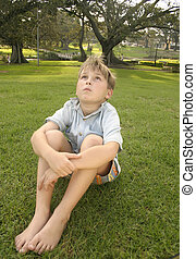 Sitting in an urban park - Young child sits in urban park....