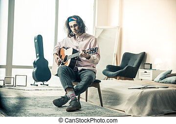 Melancholic handsome musician with wavy hair playing acoustic guitar