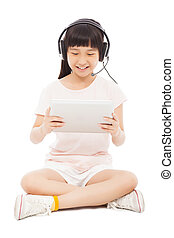 sitting little girl holding a tablet with earphone.