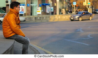 Sitting man in an orange jacket with thoughtful look, on the background of Time Lapse cars in city