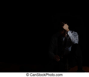 Sitting mature man holding head while holding beer bottle in dark background