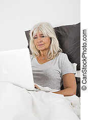 Mid Age woman with a laptop in bed