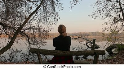 Sitting on a bench autumn scene - Young woman sitting on a ...
