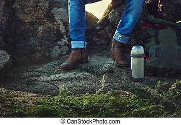 Sitting on a rock man in blue jeans and old brown shoes. Metal thermos, backpack on a foreground. Closeup of unrecognizable person