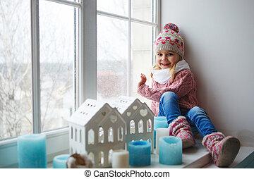 Sitting on a window sill - Little girl sitting on a window ...
