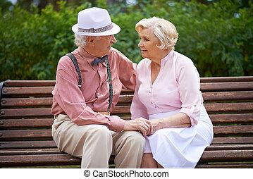 Sitting on bench - Happy seniors talking while sitting on...