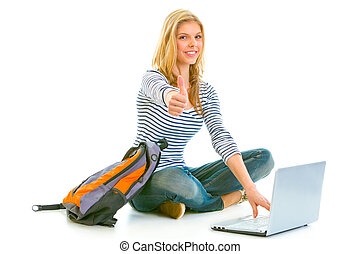 Sitting on floor with schoolbag and laptop smiling teengirl showing thumbs up gesture isolated on white