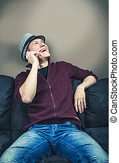 Sitting on sofa talking to phone