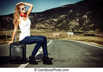 sitting on suitcase - Attractive young woman hitchhiking ...