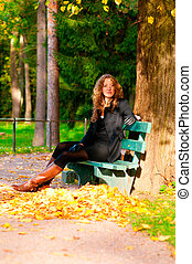 sitting on the bench in autumn park