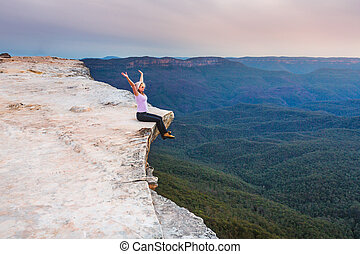 Sitting on the cliff edge feeling free - Woman showing ...